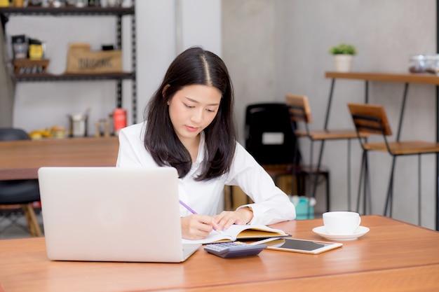 美しいアジアの若い女性は、コーヒーショップに座ってラップトップで働く。