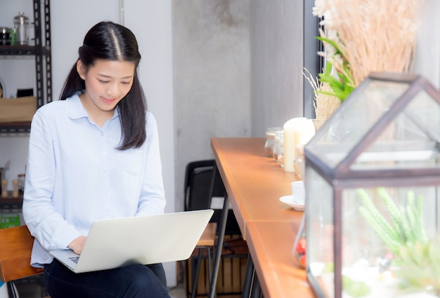 Beautiful asian young woman working online on laptop sitting at coffee shop.