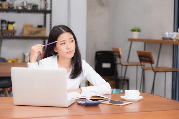美しいアジアの若い女性は、ラップトップとオンラインで作業し、現代のカフェショップでアイデアのためのプロジェクトを考える。