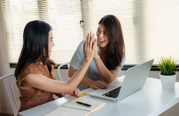 Beautiful asian young womans smiling  giving high five to together using credit card shopping online with laptop at home,  online payment