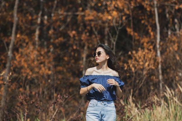 Красивая азиатская молодая женщина стоя aginst сухие листья леса