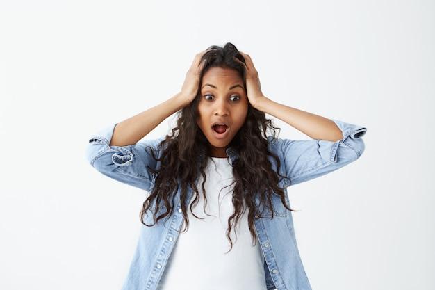 Красивая изумленная афро-американская женщина нося свободные волнистые черные волосы держа руки на ее голове с широко раскрытыми глазами и ртом будучи шокированным для того чтобы услышать новости ужаса.