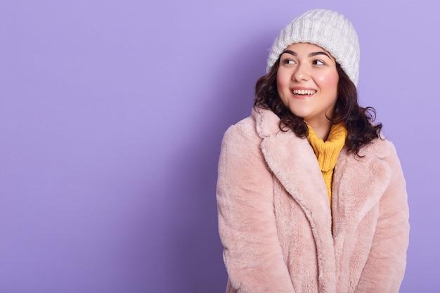 美しいびっくりした女性は淡いピンクのフェイクファーのコート、黄色いセーター、白い帽子を着ており、びっくりして笑顔に見えます