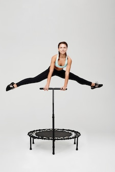 Beautiful athlete doing split jumping on rebounder holding handle