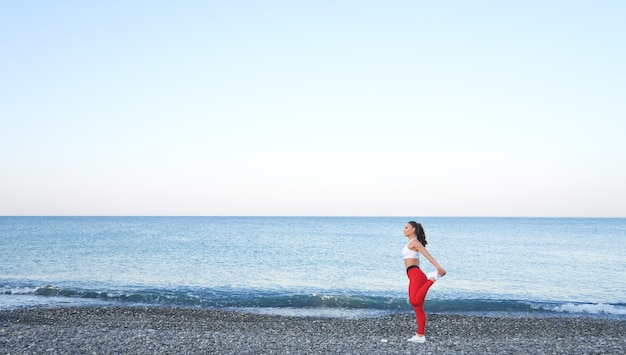 Beautiful athlete woman in red sportswear posing on the background of the sea landscape. morning workout by the ocean, healthy lifestyle