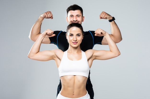 Beautiful athletic couple show biceps on gray background