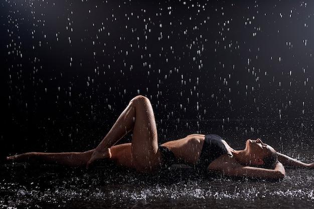 Красивая спортивная фитнес женская модель в черном нижнем белье лежит на полу под дождем
