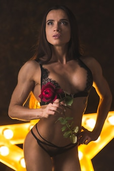 램프와 빛나는 별의 배경에 꽃 장미와 속옷에 아름 다운 운동 피트 니스 여자 보디