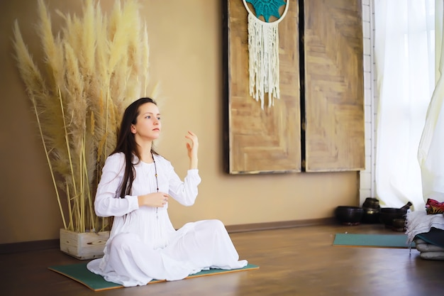 Beautiful athletic girl doing yoga exercises enjoy meditation at home. no stress, healthy habit, anxiety relief concept. lotus pose.