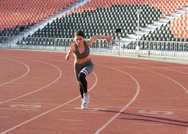 スタジアムの周りを走っている美しい運動少女