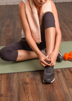 Beautiful athletic girl tying shoelaces, sitting on a mat. close-up