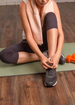 マットの上に座って、靴紐を結ぶ美しい運動少女。閉じる