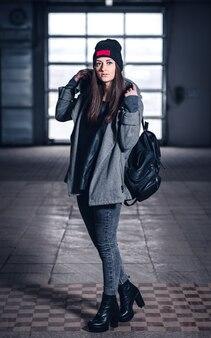 黒髪、ベニー、ホディ、産業の背景にバックパックを持つ美しいアスリートの女の子