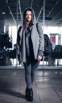 黒髪とホディオンとジムのバックパックを持つ美しいアスリートの女の子