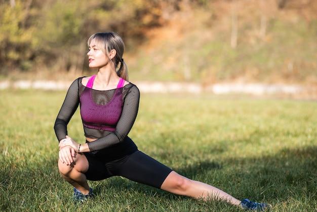 Красивая спортивная девушка с подтянутым телом в яркой спортивной одежде разминается перед фитнесом