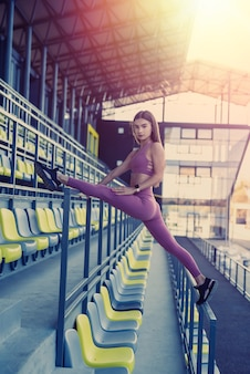 Beautiful athletic lady doing morning stretching exercises. daily workout concept