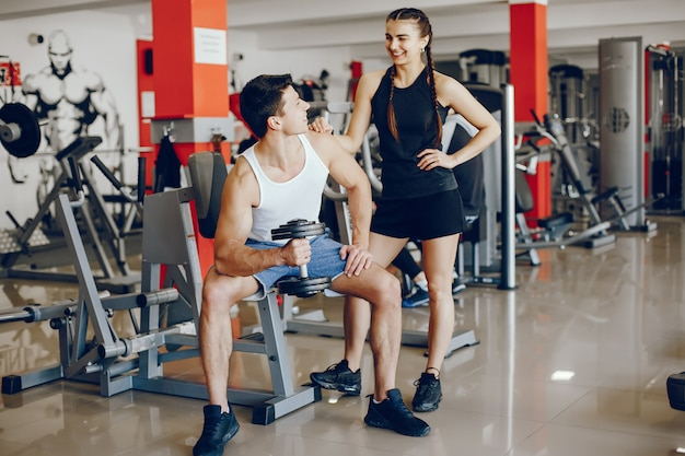 A beautiful and athletic sportswear girl training in the gym with her boyfriend