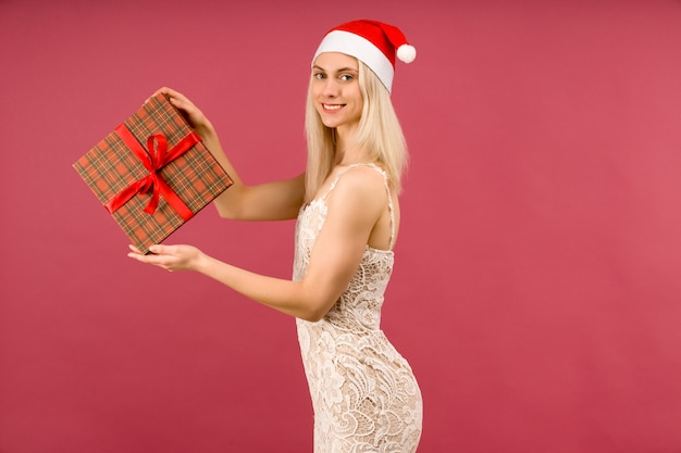 A beautiful athletic transgender man in a new year's hat and white dress, hold in hands gifts. celebration of christmas or new year on ruby background