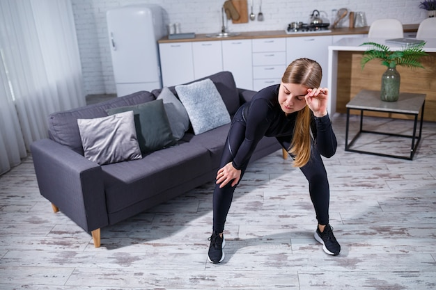 Beautiful athletic woman in black top and leggings doing sports at home. motivation to go in for sports. healthy lifestyle.