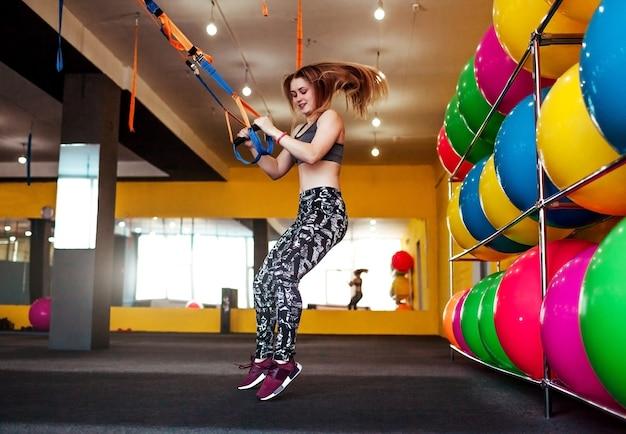 Красивая спортивная женщина делает упражнения с использованием trx в спортивной одежде в тренажерном зале