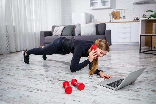 自宅でスポーツをし、電話で話している黒いトップとレギンスの美しい運動女性。スポーツに参加する動機。健康的な生活様式。