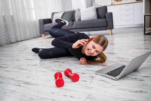 검정 상의와 레깅스를 입은 아름다운 운동 여성이 집에서 스포츠를 하고 전화 통화를 합니다. 스포츠를 하려는 동기. 건강한 생활.