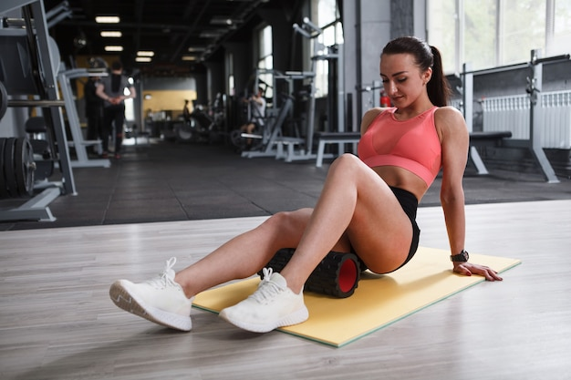 Beautiful athletic woman relaxing muscles on foam roller after exercising at gym, copy space