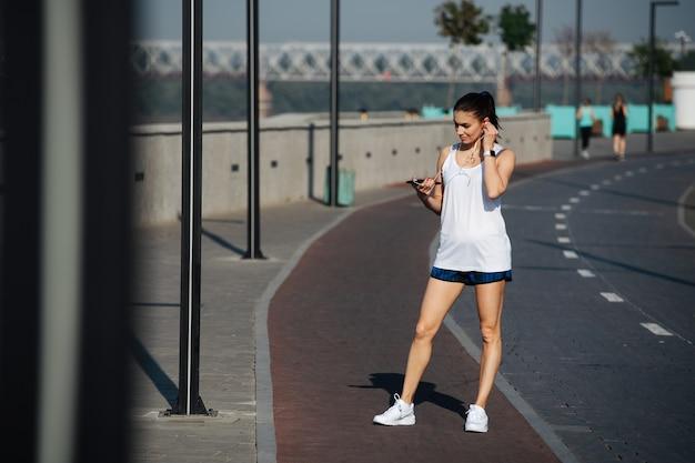 야외에서 새로운 트랙을 달리는 아름다운 운동 여성