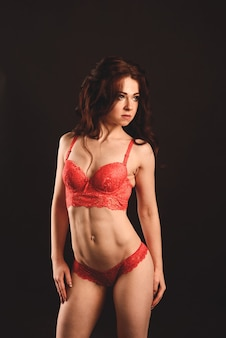Beautiful athletic woman shakes her abdominal muscles on a studio background