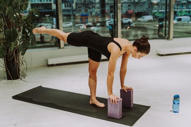 ジムでトレーニングし、トレーニングの前にストレッチ体操をしている美しい運動女性