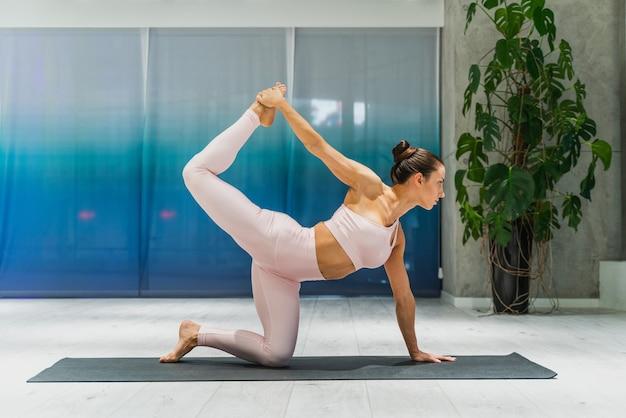 ジムでトレーニングし、トレーニングの前にストレッチ体操をしている美しいアスリート女性