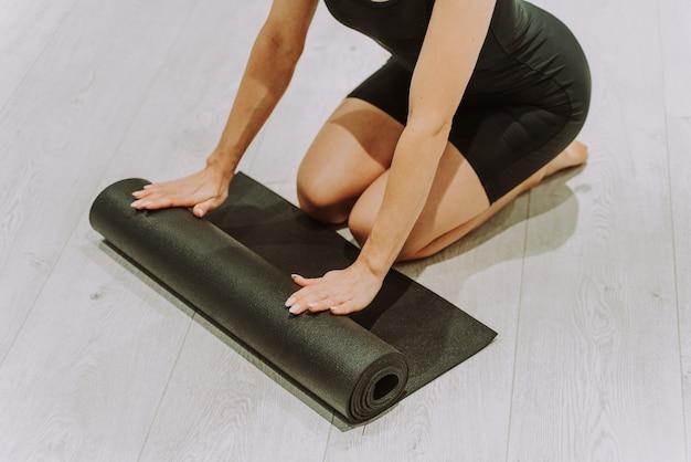 ヨガマットを広げてジムでトレーニングしている美しい運動女性
