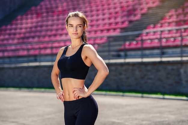 Beautiful athletic woman with fit body in black sportswear is resting after training