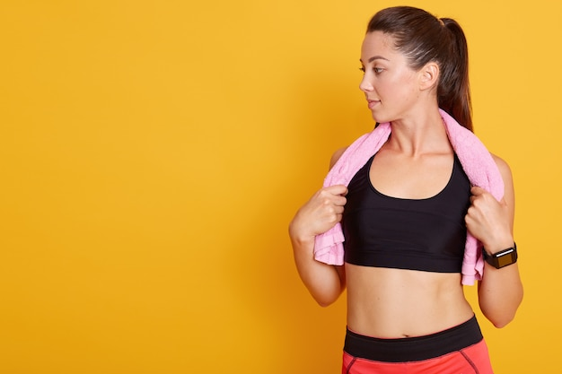 Beautiful athletic woman with rosy towel on shoulders posing isolated over yellow background, sporty female feels tired after training