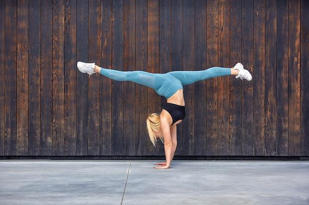 Красивая спортивная молодая гимнастка в спортивной одежде, тренировка, элемент гимнастики, делает шпагат.
