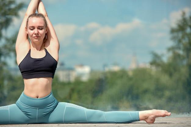 Красивая спортивная молодая девушка в спортивной одежде, делающая упражнения на растяжку на улице, элемент гимнастики, делающая шпагат