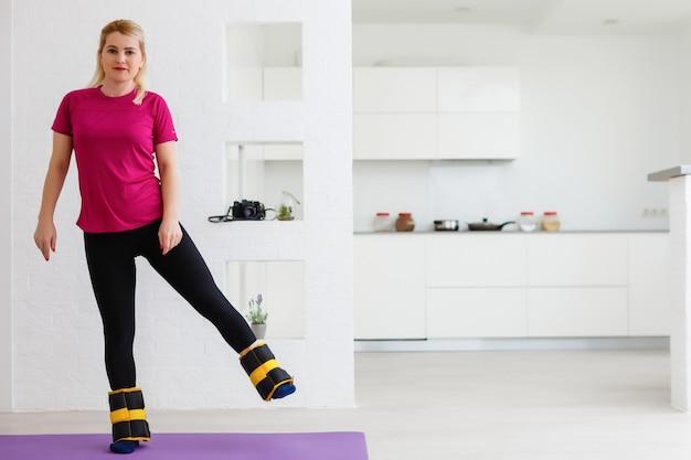美しい運動の若い現代の女性は、自宅でウェイトトレーニングに参加します
