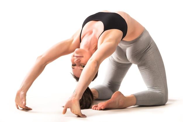 白い壁の床でsuptabhekasanaをやっている美しい運動の若い女性。血液循環と背中の健康の増加の概念。