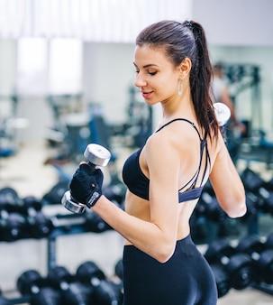ジムで運動をしている美しい運動の若い女性。筋肉質の体を持つ若い女性。フィットネスのコンセプト。