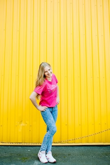 Beautiful athletic young woman with long blond hair in a pink shirt and blue jeans. in white sneakers. posing and smiling at wall of the garage on yellow wall place for text. hands on his belt