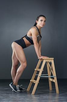체육관에서 보디빌딩 운동을 하는 근육을 가진 아름다운 운동 젊은 여성
