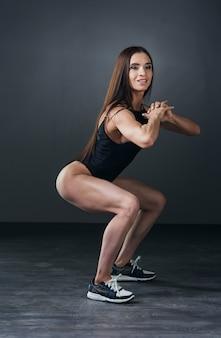 ジムでボディービルの練習をしている筋肉を持つ美しい運動の若い女性