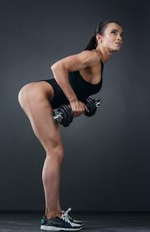 체육관에서 아령 보디빌딩으로 운동을 하는 근육을 가진 아름다운 운동 젊은 여성