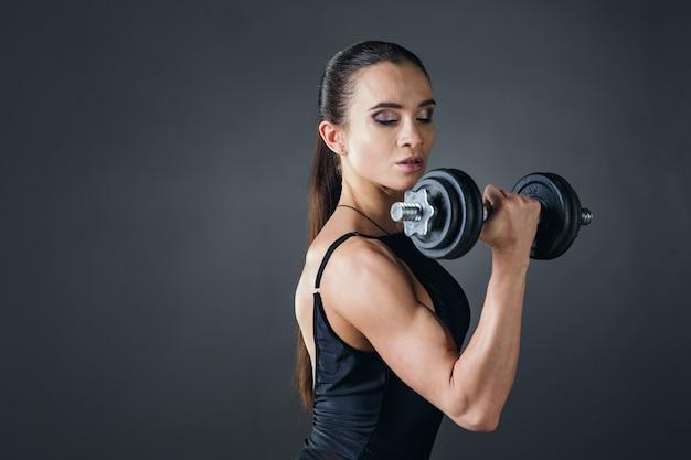 ジムでダンベルボディービルでエクササイズをしている筋肉を持つ美しい運動の若い女性