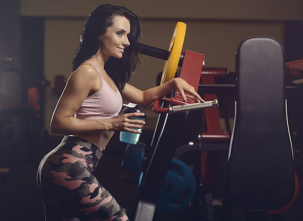 Beautiful athletic young woman working out in gym