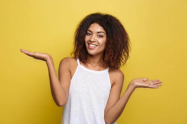 Красивая привлекательная афро-американская женщина, играющая с ее вьющимися афро-волосами. желтый фон студии. копирование пространства.