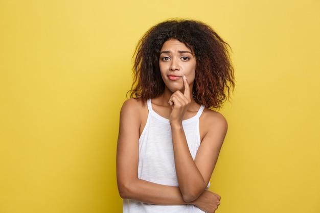 Красивая привлекательная афроамериканец женщина с модные очки, размещение на фоне желтой студии. копирование пространства.