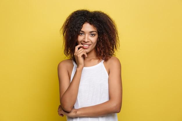 美しい魅力的なアフリカ系アメリカ人の女性は、トレンディな眼鏡を持つ黄色のスタジオの背景を掲載スペースをコピーします。