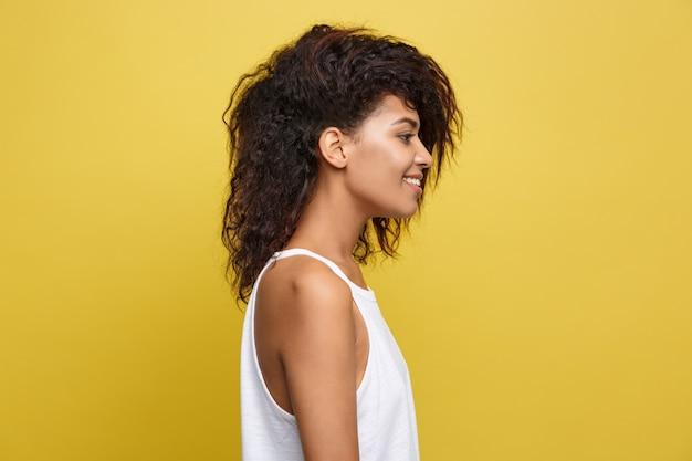 노란색 스튜디오 배경 위에 게시 유행 안경 아름 다운 매력적인 아프리카 계 미국인 여자. 공간을 복사하십시오.