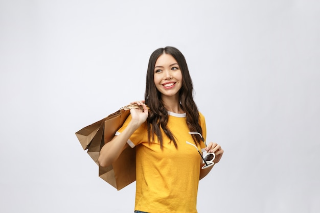 美しい魅力的なアジアの女性の笑顔と買い物袋を持っています